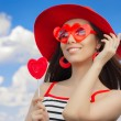 Beautiful Girl with Heart Sunglasses and, Lollipop and a Straw Hat on Blue Sky — Stock Photo #62733081