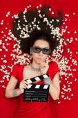 Puzzled Girl with 3D Cinema Glasses,  Popcorn and Director Clapboard — Stock Photo