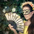 Beautiful Woman with Floral Wreath, Mask and Fan — Stock Photo #78482928