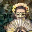 Beautiful Woman with Floral Wreath, Mask and Fan — Stock Photo #78482932