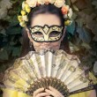 Beautiful Woman with Floral Wreath, Mask and Fan — Stock Photo #78482942