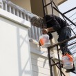 Worker on scaffold holding brush painting wall — Stock Photo #63989629