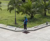 Worker use lawnmower to trim grass  — Zdjęcie stockowe
