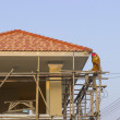 Man worker on scaffold painting roof — Stock Photo #63990177