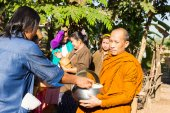 People put food on buddhist monk alms bowl — Stock Photo