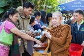 Ludzie umieścić żywności na miską żebraczą mnich buddyjski — Zdjęcie stockowe
