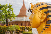 Left side of golden pharaoh statue with pagoda background — Stock Photo
