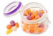 Caramelle colorate in vaso di vetro su sfondo bianco — Foto Stock