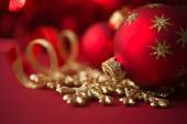 Red and golden christmas ornaments on red xmas background — Stock Photo