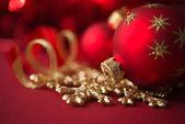 Enfeites de Natal de vermelho e dourado sobre fundo vermelho xmas — Fotografia Stock