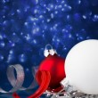 White, silver and red christmas ornaments on dark blue bokeh background with space for text — Stock Photo #57830361
