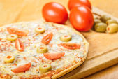 Fresh pizza  on wooden table — Stock Photo