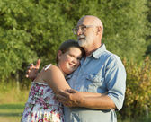 Outdoor portrait of  grandfather with granddaughter. — Stock Photo