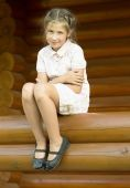 The girl is sittind on a log. — Stock Photo