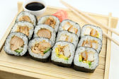 Breaded and teriyaki chicken sushi on bamboo tray against white  — Photo