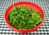 Chopped mustard greens in a red strainer bowl — Stock Photo