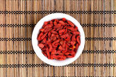 Goji berries in white bowl on oriental mat — Stock Photo