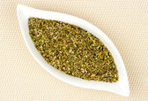 Dried and chopped oregano in stylish glass container — Stock Photo