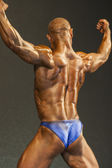 Bodybuilder On Stage Demonstrating His Body and Muscles Standing Turned Backwards — Stock Photo