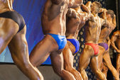 Bodybuilders On Stage Demonstrating Body and Muscles Standing Turned Backwards — Stock Photo