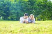 Happy Caucasian Couple in Love Lying on the Grass Outdoors. Read — Stock Photo