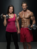 Athletic Man And Woman With A Dumbells — Stock Photo