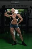 Woman Bodybuilder Performing Front Biceps Pose — Stock Photo