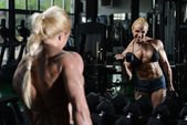 Woman Bodybuilder Exercising Biceps With Dumbbells — Zdjęcie stockowe