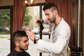 Male Hairdresser Cutting Hair Of Smiling Man Client — Stock Photo