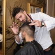 Male Hairdresser Cutting Hair Of Smiling Man Client — Stock Photo #55750973