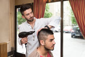 Stylist Drying Hair Of A Male Client — Stockfoto