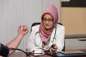 Muslim Doctor Taking Young Man's Blood Pressure — Stock Photo