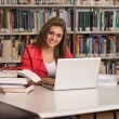 Happy Female Student Working With Laptop In Library — Stock Photo #58472267