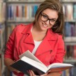 Pretty Young College Student In A Library — Stock Photo #58473483