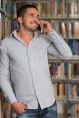 Handsome College Student Using Mobile Phone In Library — Stock Photo