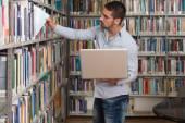 Estudiante masculino feliz de trabajar con el portátil en la biblioteca — Foto de Stock