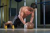 Attractive Male Athlete Performing Push-Ups On Medicine Ball — Stock Photo