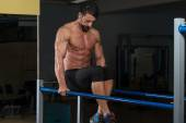 Bodybuilder Exercising On Parallel Bars — Stock Photo