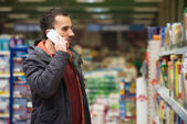 英俊的男人,在手机上超市 — 图库照片