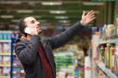 Süpermarkette cep telefonunda yakışıklı adam — Stok fotoğraf