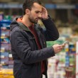 Man Looking Confused At Mobile Phone In Supermarket — Stock Photo #62130383