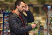 Man Looking Confused At Mobile Phone In Supermarket — Stock Photo