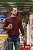 年轻男子在超市在手机上键入 — 图库照片