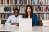 Mutlu öğrenciler dizüstü bilgisayar kitaplığı ile çalışma — Stok fotoğraf