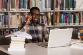 Male Student Talking On The Phone In Library — Stock Photo