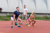 Two People Doing Kettlebell Exercise Outdoor With Instructor — Fotografia Stock