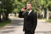 Young Businessman On The Phone Outdoors In Park — Stock Photo