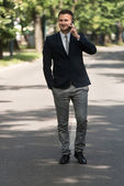 Businessman Walking Outside In Park While Using Mobilephone — Stock Photo