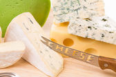 Delicious cheese and knife on wood platter. — Stock Photo