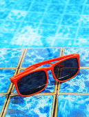 Sunglasses in the pool with blue water — Stock Photo